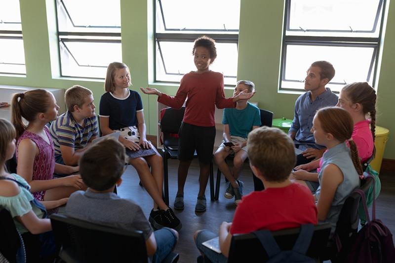 Gruppe von Grundschulkindern, die auf Stühlen im Kreis sitzen, während ein Mädchen steht und spricht
