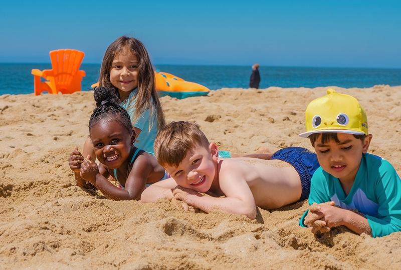 Gruppe von Kindern, die im Sand am Meer liegen