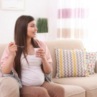 Junge schwangere Frau sitzt auf dem Sofa und isst Joghurt