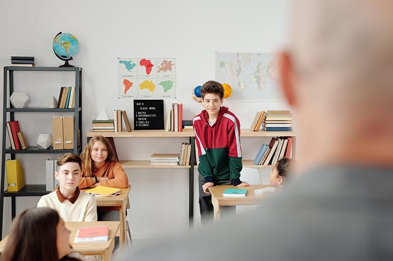 Junge in einem Hoodie, der im Klassenzimmer steht und lächelt