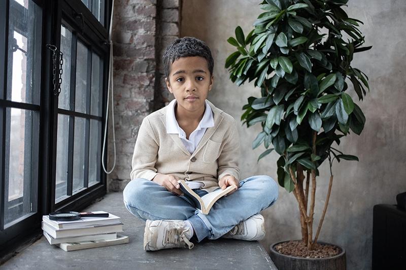 Junge sitzt auf der Fensterbank und hält ein Buch in der Hand