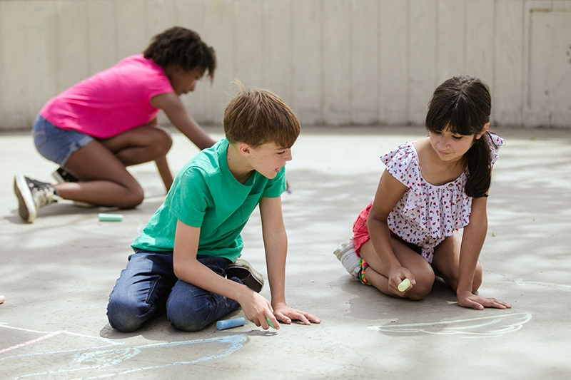 Junge und Mädchen reden beim Zeichnen mit Kreide auf Beton