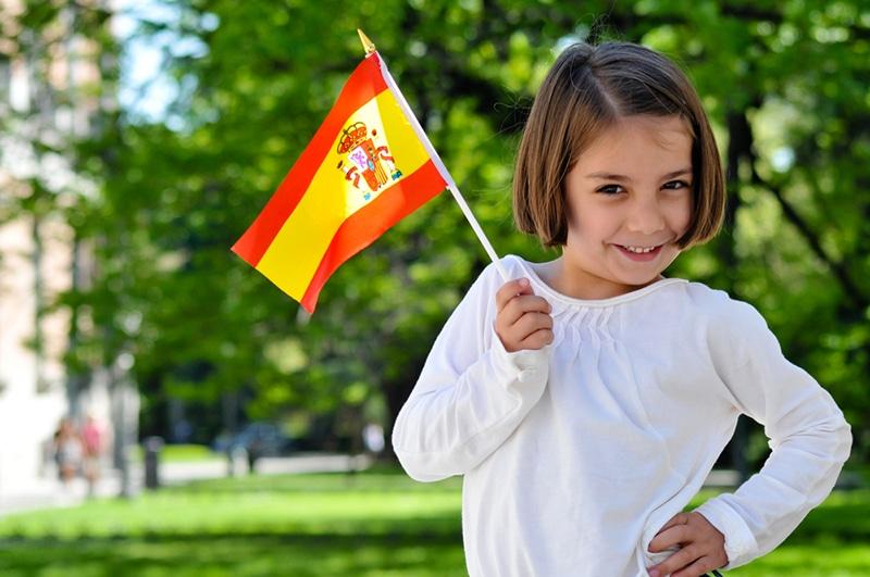 Junges Mädchen mit spanischer Flagge steht im Park