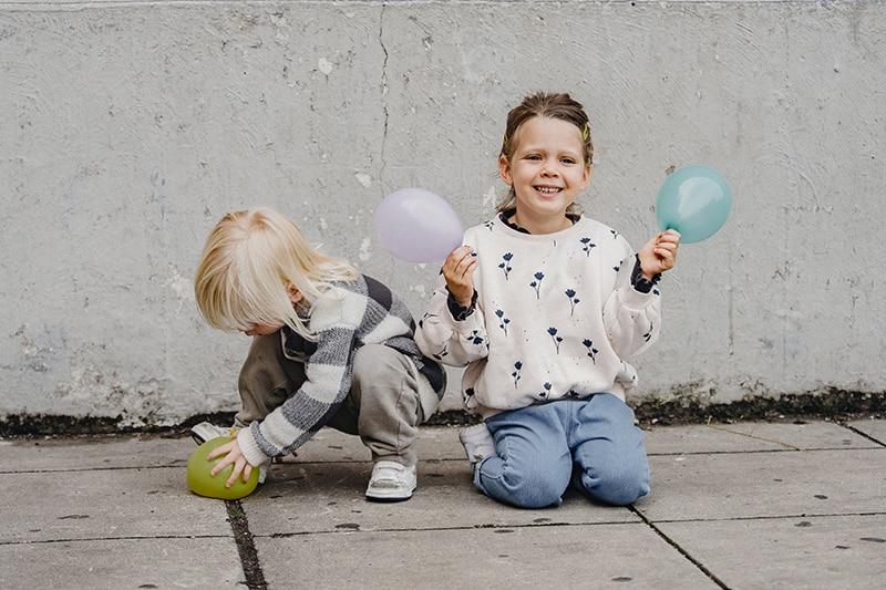 Kinder, die Luftballons halten, während sie auf dem Betonboden sitzen
