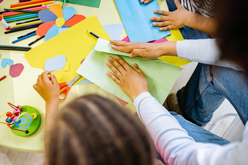 Kinder, die im Klassenzimmer Kunst mit farbigem Papier machen