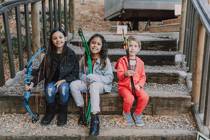 Kinder mit Pfeil und Bogen sitzen auf der Treppe