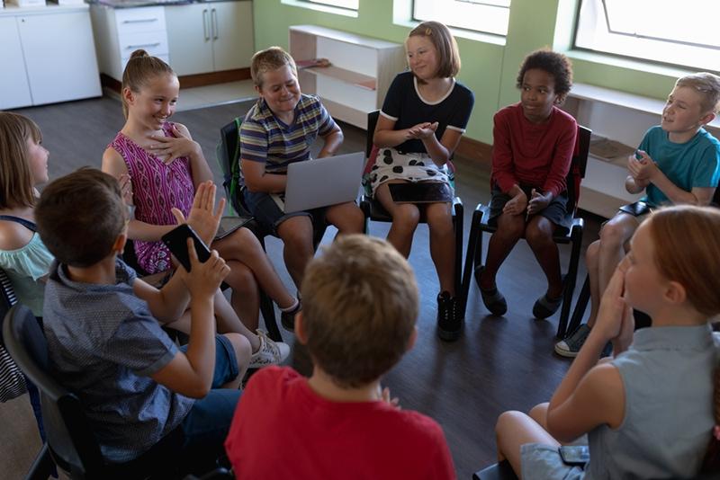 Kinder sitzen auf Stühlen im Kreis im Klassenzimmer