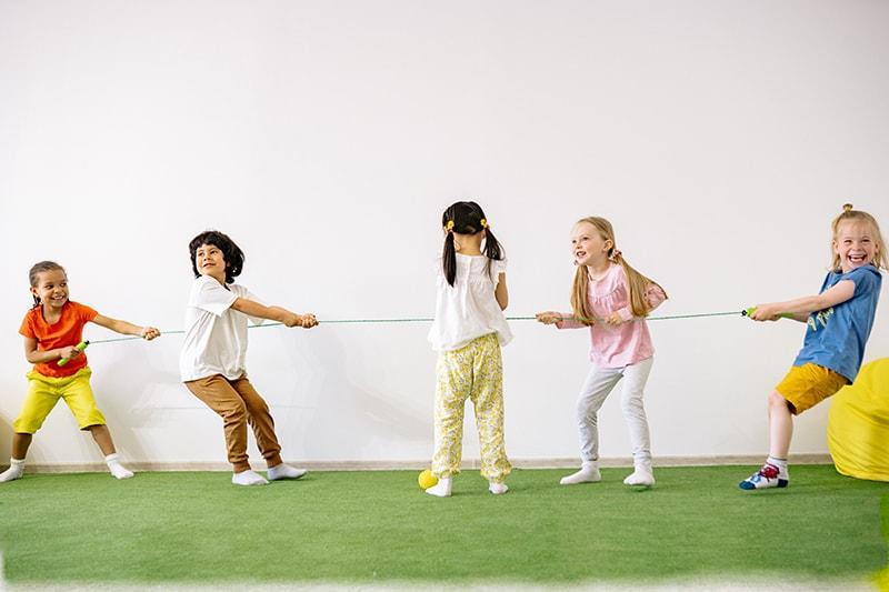 Kinder spielen Tauziehen im Zimmer