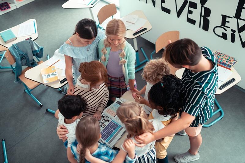 Kinder stehen im Kreis um den Schreibtisch im Klassenzimmer