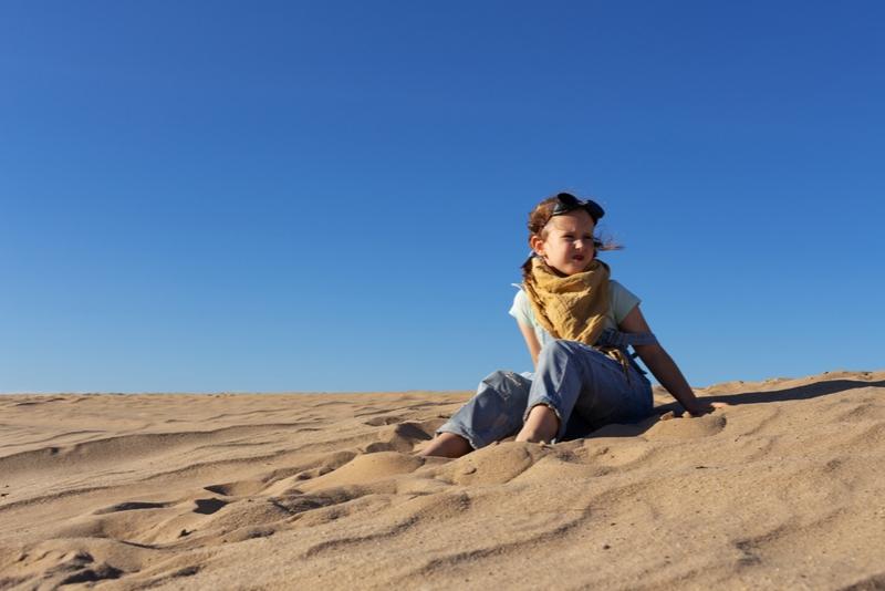 Kleines Kindermädchen, das in der Sandwüste sitzt