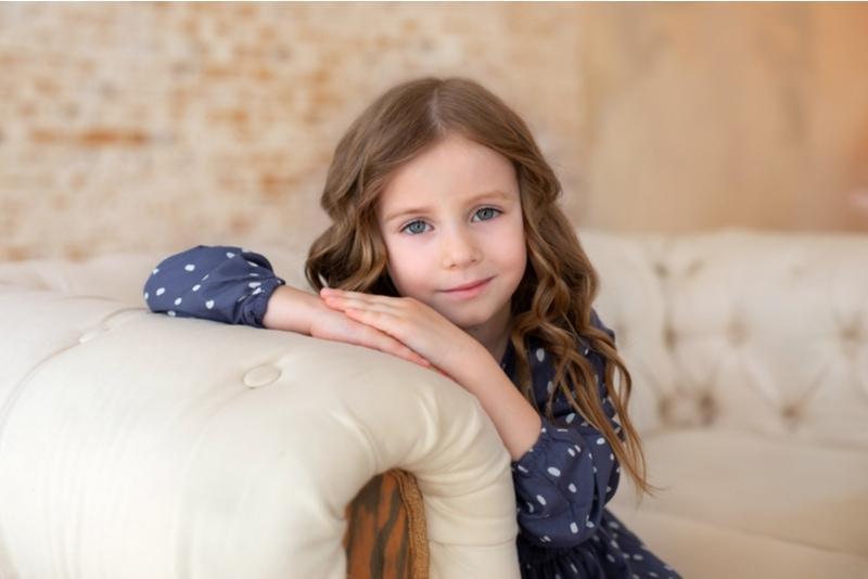 Lächelndes kleines Mädchen sitzt auf einer Couch im Wohnzimmer