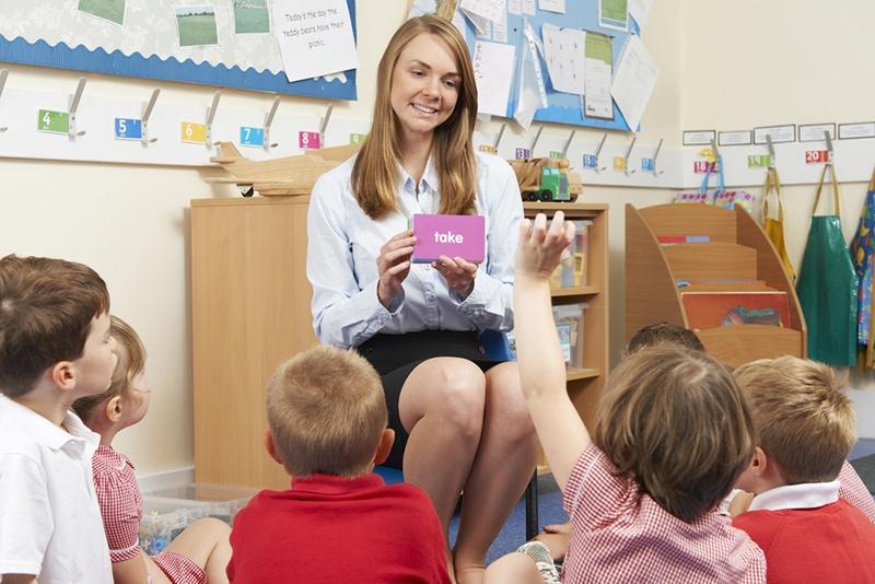 Lehrer zeigt der Grundschulklasse im Klassenzimmer Flash-Karten