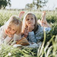 zwei kleine Mädchen lesen Buch auf einem Feld