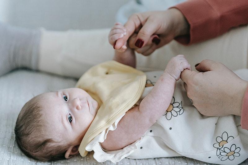 Mama hält süßes Baby für die Hände auf dem Bett
