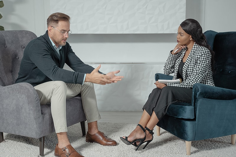 Mann, der mit einer Therapeutin spricht, während er im Sessel sitzt