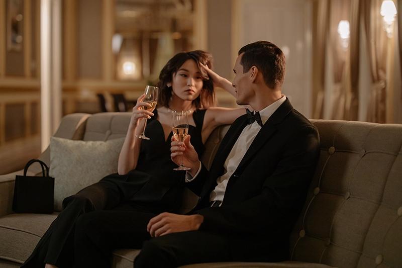 Mann und Frau stoßen mit Champagner an, während sie auf der Couch sitzen
