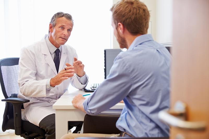 Männlicher Patient in Konsultation mit Arzt im Büro