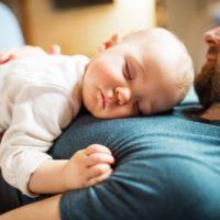 kleines Mädchen schläft auf der Brust ihres Vaters