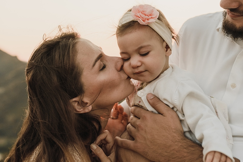 Mutter küsst ihr Baby, während der Vater sie in den Armen hält