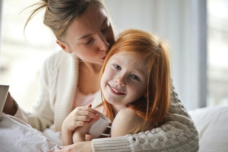 Mutter küsst ihre kleine Tochter mit roten Haaren