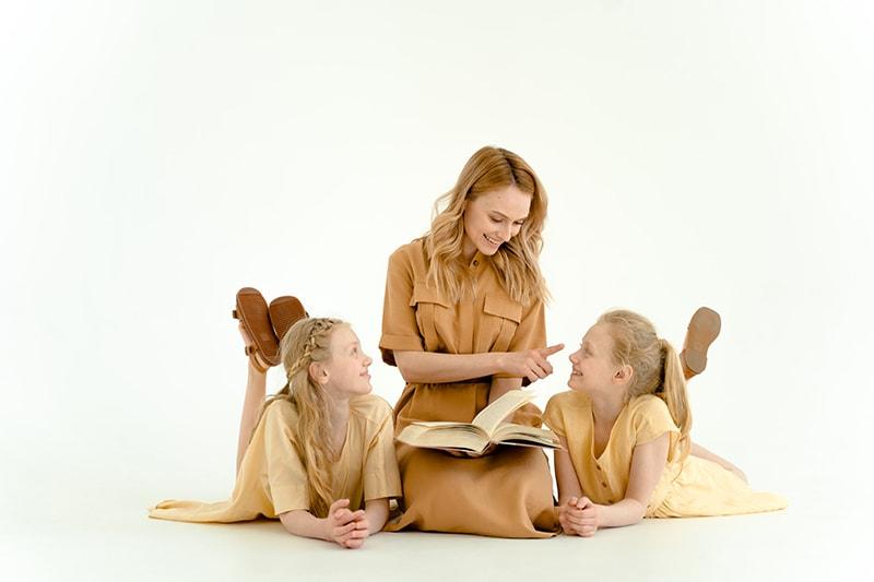 Mutter lacht mit ihren Töchtern, während sie ein Buch hält