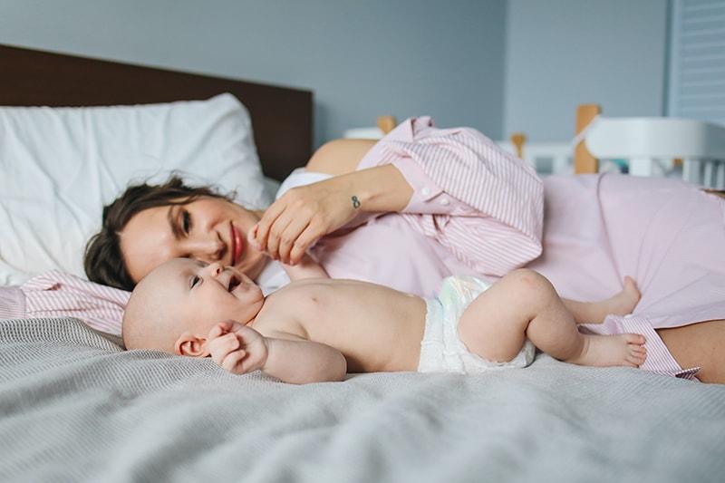 Mutter liegt neben ihrem Baby auf dem Bett