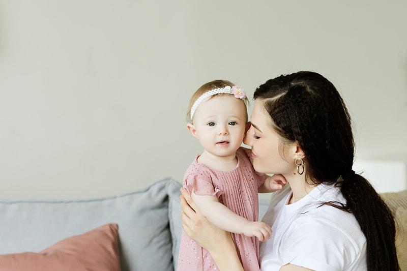 Mutter mit süßem Baby im rosa Kleid