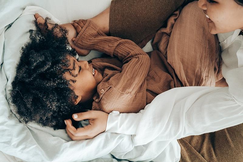 Mutter spielt mit Kind auf dem Bett