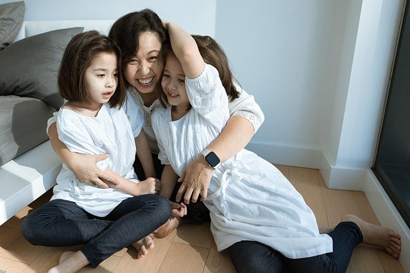 Mutter umarmt ihre lächelnden Töchter, während sie im Wohnzimmer sitzt