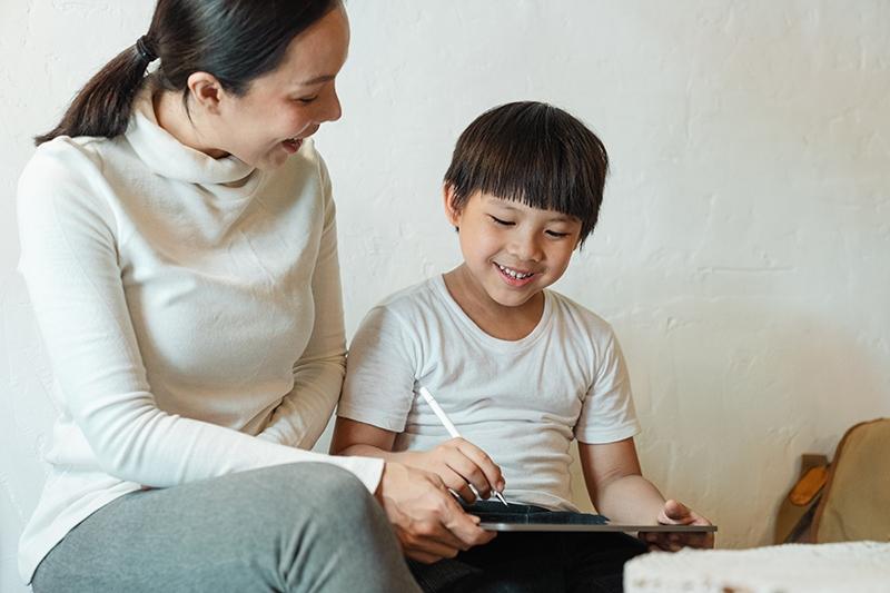 Mutter und Sohn lachen beim Benutzen des iPad