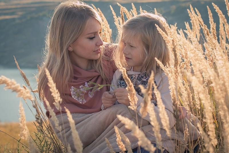 Mutter und kleine Tochter sitzen an einem sonnigen Tag auf dem Feld