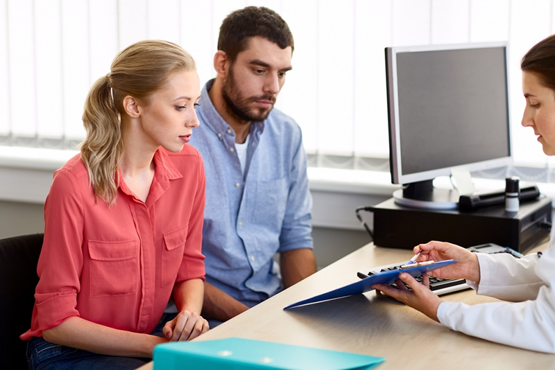 Paar hört einem Arzt zu, der ihnen die Ergebnisse in der Fruchtbarkeitsklinik zeigt