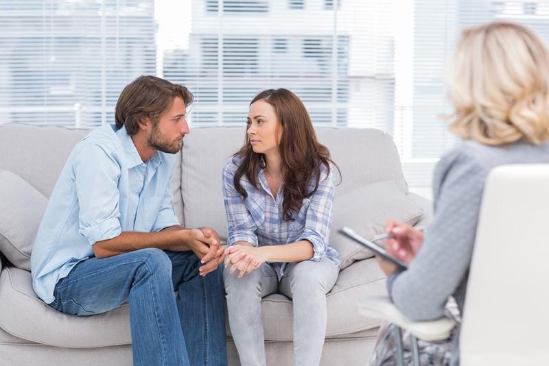 Paar redet und sitzt auf der Couch beim Therapeutenv