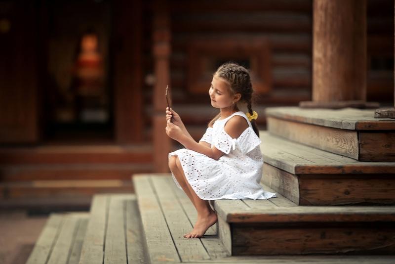 Porträt eines kleinen Mädchens, das sich im Spiegel schaut