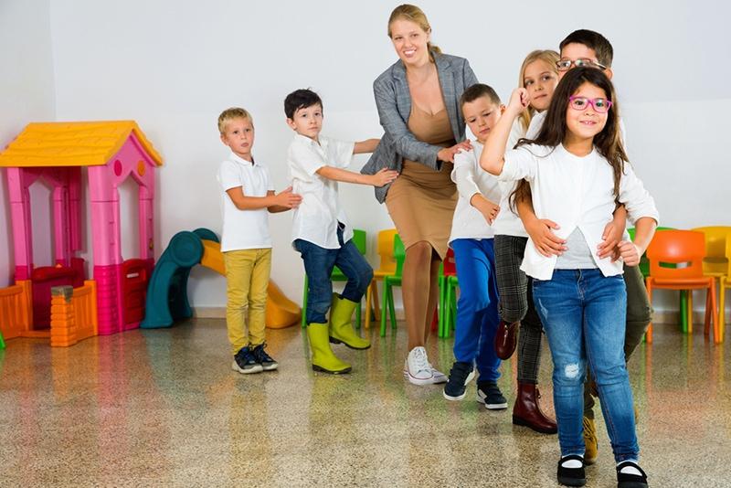 Positive Lehrerin, die Kreisspiel mit Kindern im Klassenzimmer spielt