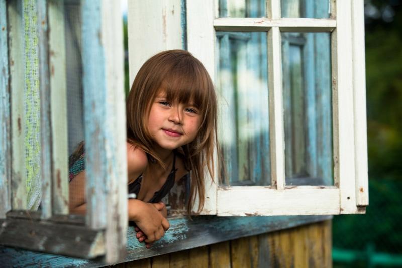Schönes kleines Mädchen schaut aus dem Fenster