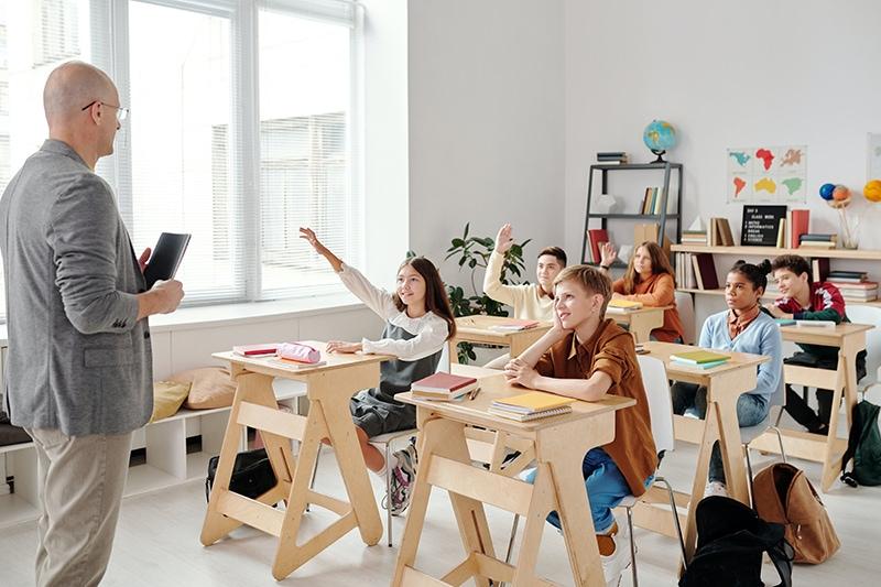 Schüler heben die Hände im Klassenzimmer