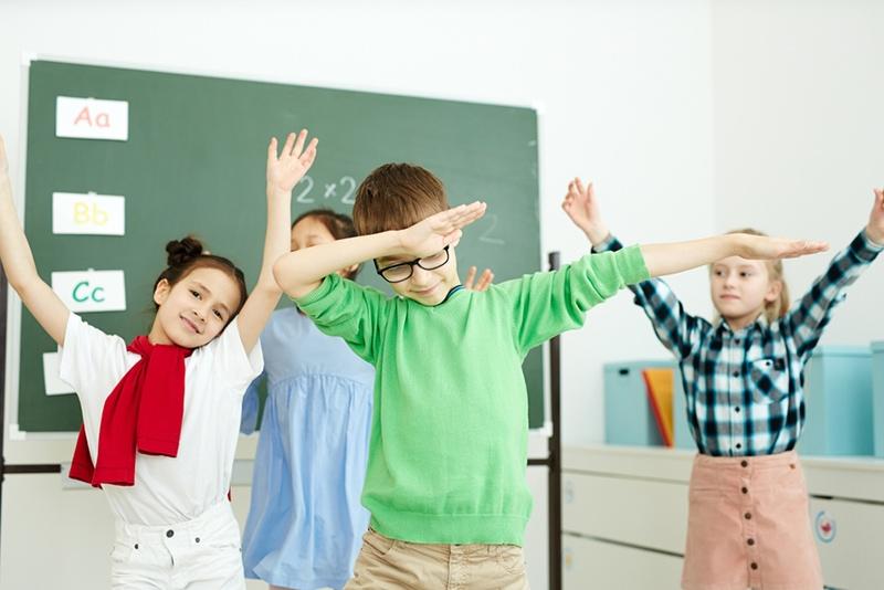 Schulkinder tanzen im Klassenzimmer