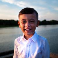 lächelnder kleiner Junge, der in der Nähe des Sees steht