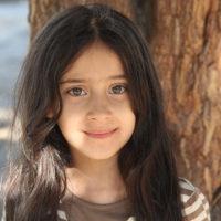 süßes Mädchen, das in der Nähe des Baumes steht