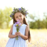 kleines Mädchen mit einer Blumenkrone auf dem Kopf, das draußen mit einem Blumenstrauß steht