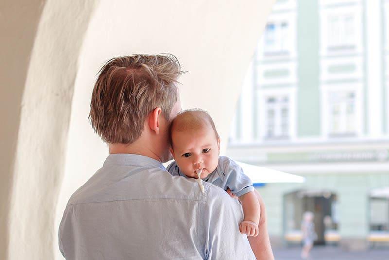 Vater hält Baby, das Milch aus dem Mund spuckt