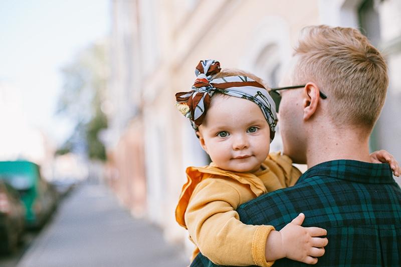 Vater mit süßem Baby im gelben Pullover