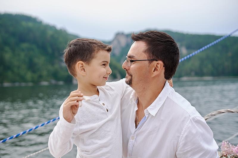 Vater umarmt seinen lächelnden Sohn am Meer