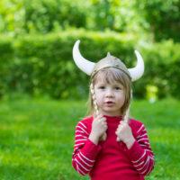 blondes kleines Mädchen im roten Hemd mit Wikingerhut steht draußen