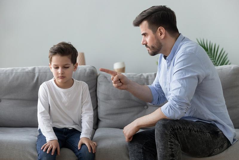 Wütender Vater schimpft mit dem traurigen Jungen, der neben ihm auf der Couch sitzt