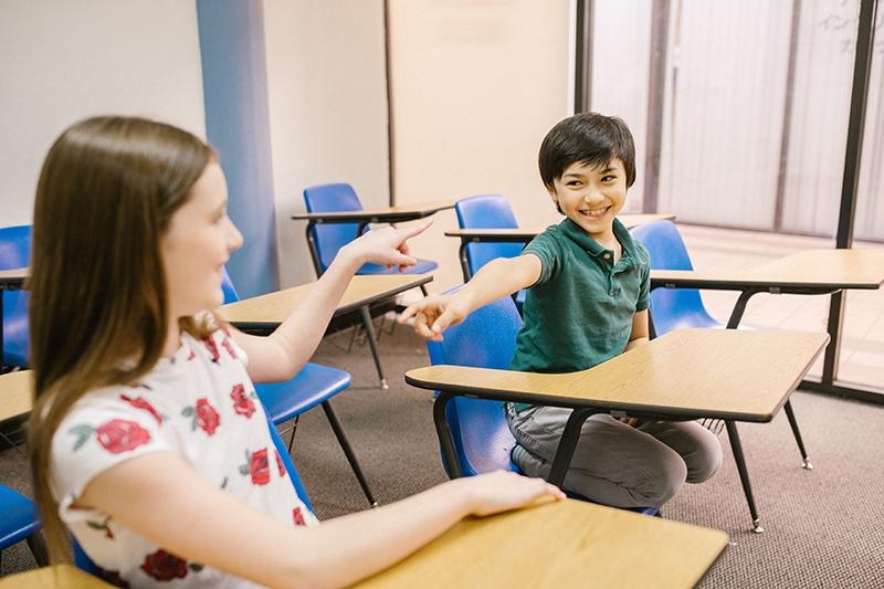 zwei fröhliche Kinder, die im Klassenzimmer aufeinander zeigen