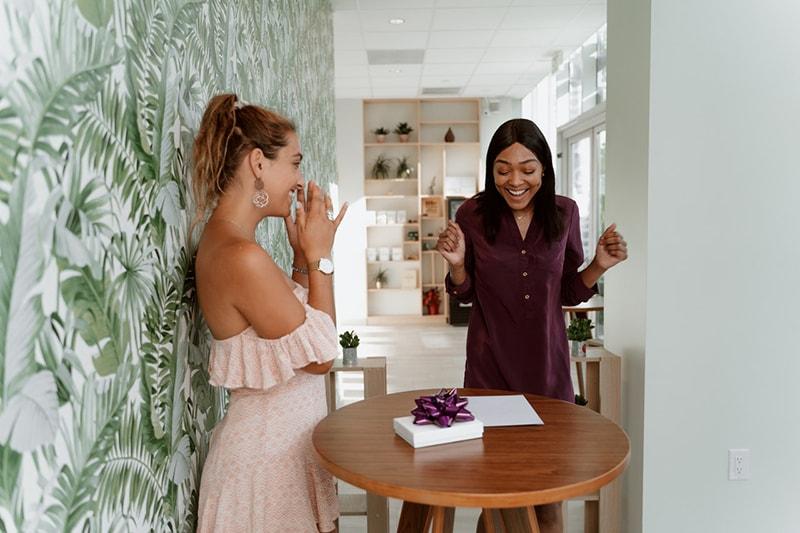 Zwei glückliche Frauen, die Geburtstag feiern und sich über das Geschenk freuen