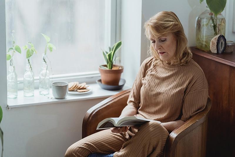 ältere frau, die ein buch liest, während sie zu hause im sessel sitzt