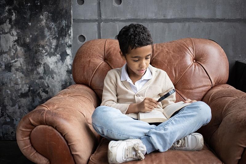 arabischer schüler mit einer lupe ein buch lesen